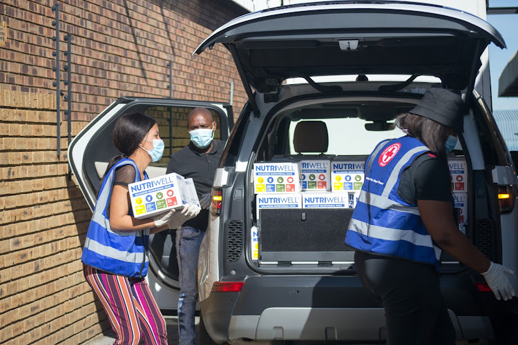 Red Cross workers use Land Rovers to distribute Nutriwell packages to schools, orphanages and old age homes.
