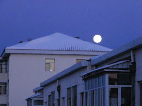 Photo: A late full bright moon above roof of residential building.