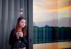 meisje met kopje koffie staart tussen de schuifdeuren naar buiten