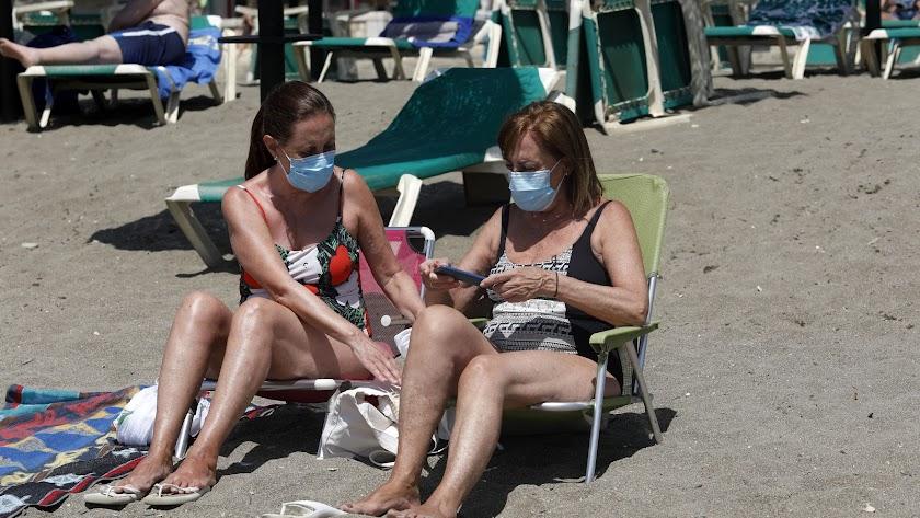 Dos mujeres con mascarillas en la playa de La Malagueta.