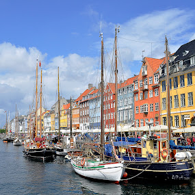 Nyhavn, Copenhagen, Denmark by Steve Corcoran - Travel Locations Landmarks ( clouds, copenhagen, harbor, boats, harbour, docks, dockside, coloured houses, hynavn, wooden ships, sky, colored houses, townhouses, ships, denmark, waterfront )