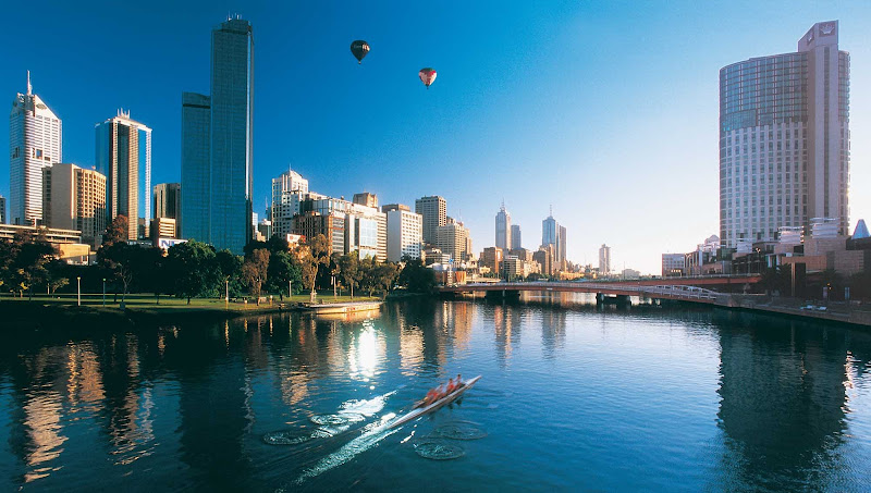 Rowers and hot air balloons over the Melbourne skyline and Yarra River.