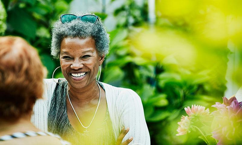 mujer feliz de mediana edad hablando al aire libre bajo la luz del sol