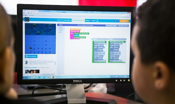 A child and his instructor look at lessons online during a coding class.