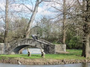 Photo: Crane flying over a stone bridge and pond at Eastwood Park in Dayton, Ohio.
