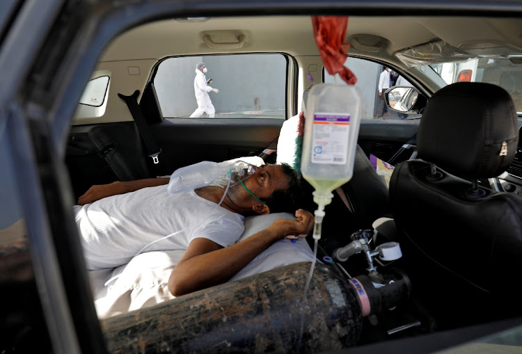 A Covid-19 patient inside a car while waiting to enter a hospital for treatment amid the out-of-control spread of the coronavirus, in Ahmedabad, India, April 22 2021. Picture: REUTERS/AMIT DAVE