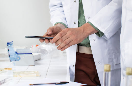 Two men in lab coats working in a science lab and using a smartphone.