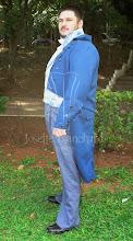 Photo: Figurino Masculino Império.  Camisa império em algodão com jabbot em linho branco, calça longa império em gabardine cinza azulado, colete império em brocado azul claro, casaca império em oxford azul petróleo. A partir de R$ 600,00.