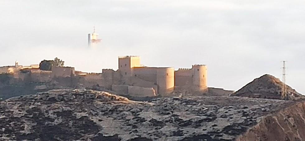 La imponente silueta de la Alcazaba rodeada por la niebla y el perfil de la torre de salvamento, en una fotografía de Antonio Martínez