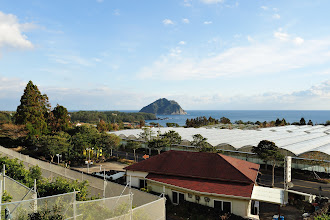 Photo: The living room came with panels of floor-to-ceiling windows. Outside, there was a balcony overlooking a restaurant specialized in Korean BBQ (closest to our apartment), a tangerine plantation across the road (covered in white ceiling), and a huge rock at the sea.