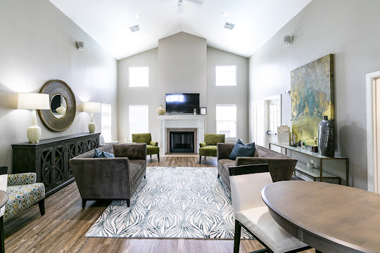 Clubhouse with neutral walls, wood-inspired flooring, fireplace, large windows, and flatscreen TV