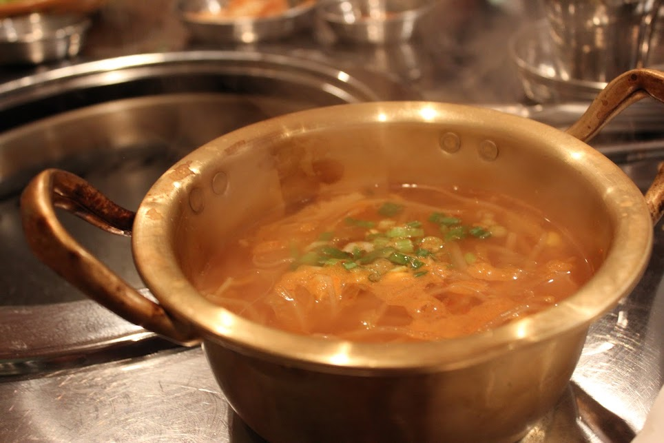 Spicy soup in a gold bowl at kookminhakgyo