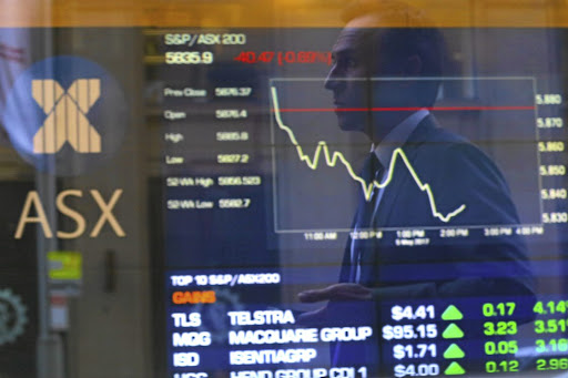 An investor is reflected in a window in front of a display of stock prices at the Australian Securities Exchange in Sydney.     File picture: REUTERS