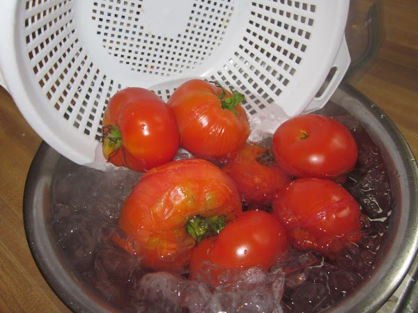 Remove tomatos from the water with the slotted spoon and dip them into the...