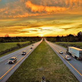 Traveling into the Sunset. by Jim Dawson - Transportation Roads ( sunset. trucks. cars. clouds. median. vanishing_point. )