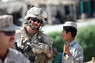 Photo: U.S. Marine Gunnery Sgt. Mike Brown, security detail, 1st Battalion, 3rd Marine Regiment, talks to one of the local Afghan children at a bazar in Nawa, Afghanistan, where U.S. Marine Brig. Gen. Joseph L. Osterman, Commanding General 1st Marine Division Foward (1st MarDiv (Fwd), was visiting, April 18, 2010. Brig. Gen. Osterman was there to participate in the re-opening of a newly refurbished district administration building in support of the International Security Assistance Force. (U.S. Marines Photo by SSgt. Ezekiel R. Kitandwe /Released)