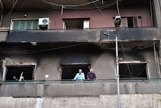 Photo: The inhabitants of the apartment stare out below from the balcony of the burnt building...