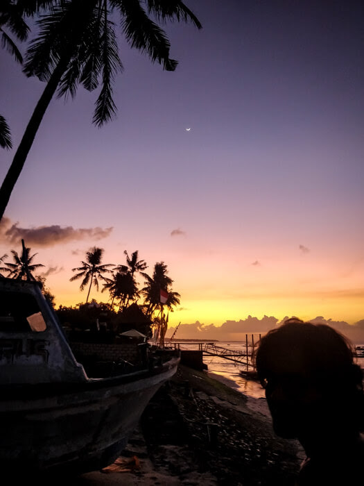 A boat, a moon. and twilight colors after a gorgeous sunset in the island nusa penida bali