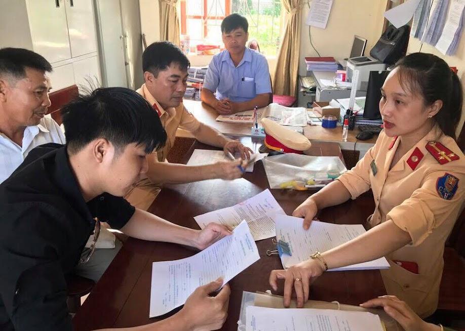 Cán bộ Đội CSGT-TT Công an huyện hướng dẫn người dân làm thủ tục đăng ký phương tiện