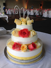 Photo: 3-tier wedding cake featuring totally smooth frosting w/o borders, silver diamond and yellow ribbon combo wrap around the bottom of each tier w/fresh yellow and peach colored roses (provided by customer).