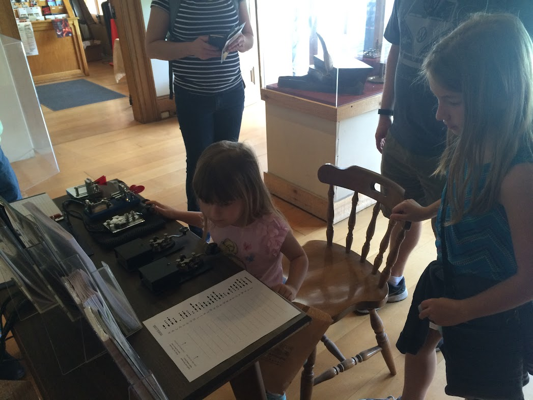 Young people were especially interested in the Morse Code Practice Station.   Here a young lady (YL) is learning Morse Code at the Pony Express Terminal NPOTA/Special Event Station N6P. (photo by Bob Woodward N6PGQ)