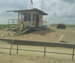 Photo: The lifeguards down the beach watching proceedings, making sure the small crowd doesn't endanger themselves.