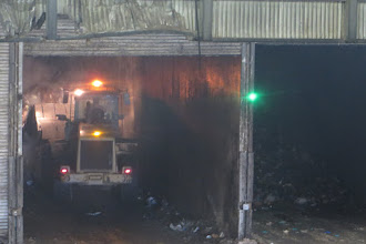 Photo: Tunnel for composting green waste. Note steam rising from pile behind truck