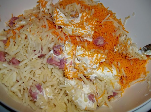In a large bowl, mix hash browns, soups, onion, ham, cheddar cheese, sour cream,...