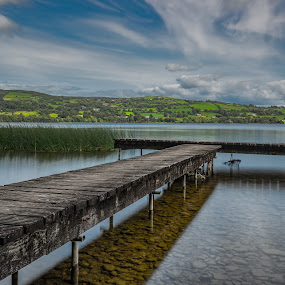 Fishing Stand Lough Derg by John Holmes - Buildings & Architecture Bridges & Suspended Structures ( sky, reeds, stones, wood, clouds, long exposure, lake, water, fishing stand, lough derg, structure )