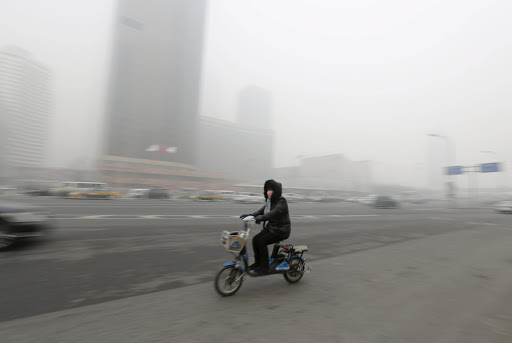 A woman wearing a mask cycles amid heavy smog in Beijing's Guomao area, China. REUTERS/ JASON LEE