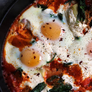 Sicilian Baked Eggs with Artichokes, Burrata, Spinach, and Spicy Tomato Sauce.