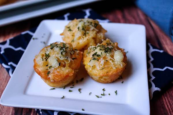 Three Mac And Cheese Bites On A Plate.