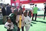 Comrades Marathon winner Edward Mothibi poses with his three daughters after winning the men's race in Durban on June 9 2019.