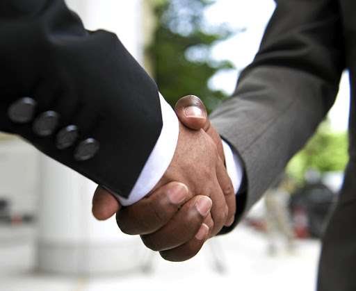 A black businessman shakes the hand of a white colleague after concluding a business deal. / Supplied