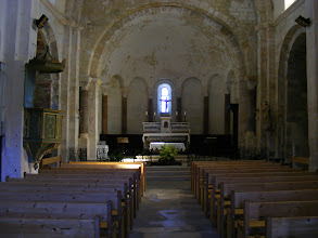 Photo: The church interior, with the lighting typical of the small windows in Romanesque architecture.