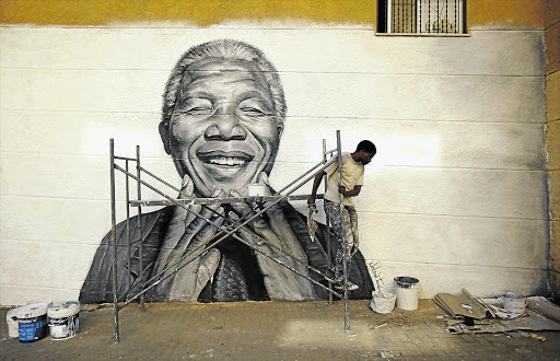 Nelson Tavares, 24, works on a mural of Nelson Mandela in his neighbourhood in Lisbon, Portugal. Mandela was yesterday discharged from hospital after almost three months of being treated for a lung infection.