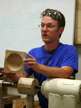 Photo: Our Demonstrator for the evening is Mark Gardner, a well-known and highly respected wood artist, who is visiting from North Carolina to teach turning classes at the Woodworkers Club.  Here he shows the beginning (on the lathe) and the end (in his hands) of a process for making a 3-axis square bowl.