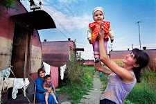 vrouw houdt trots baby omhoog een andere zit met kind op schoot naast een ijzeren woning