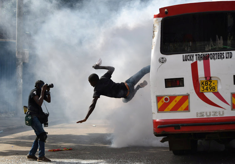 A supporter of Kenyan opposition leader Raila Odinga jumps from a bus after riot police fired teargas canisters to disperse them after his swearing-in ceremony in Nairobi.