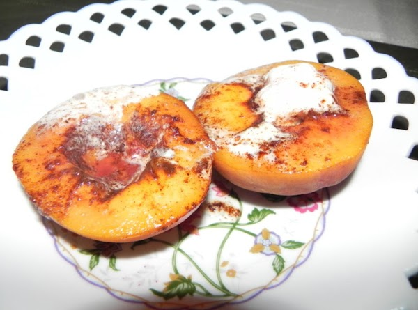 Slice peaches in half and remove the pit. Heat some butter in a small...