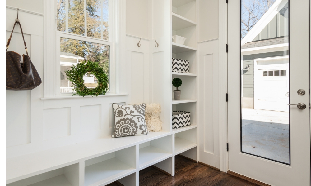 Shelving that is white and organized by an entryway