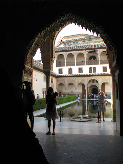 From the shadows, looking at the courtyard in La Alhambra, Granada