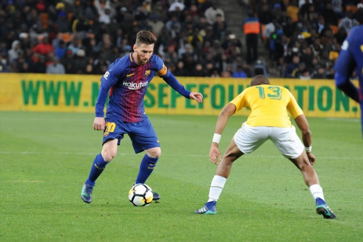 Barcelona's Argentine soccer star Lionel Messi and Tiyani Mabunda of Mamelodi Sundowns during the International Club Friendly match between Mamelodi Sundowns and Barcelona FC at FNB Stadium on May 16, 2018 in Johannesburg, South Africa.