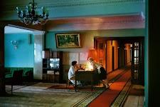 2 vrouwelijke personeelsleden van een hotel(?) in gesprek; de een zit aan een kleine desk, de ander hangt er over heen