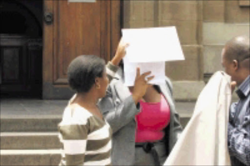 FACELESS: A friend hides Nompumelelo Ntshiza's face after her ex-husband Victor Akpanta Usen's case was postponed yesterday. 04/12/08. Pic. Bafana Mahlangu. © Sowetan.