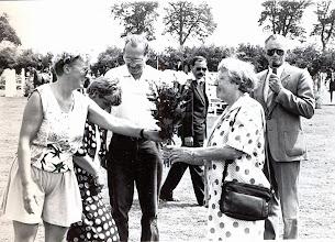 Photo: V.V.V. Anne Hofsteenge wordt namens de voorzitter Machienus Jobing bedankt voor zijn jarenlange inzet als hoefsmid tijdens het concours op tweede pinksterdag. Gretha Nijhof-Vedder overhandigd de bloemen aan zijn vrouw Tiny.
