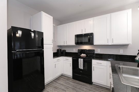 Fully-equipped kitchen with wood-inspired flooring, white cabinets, and stainless steel appliances