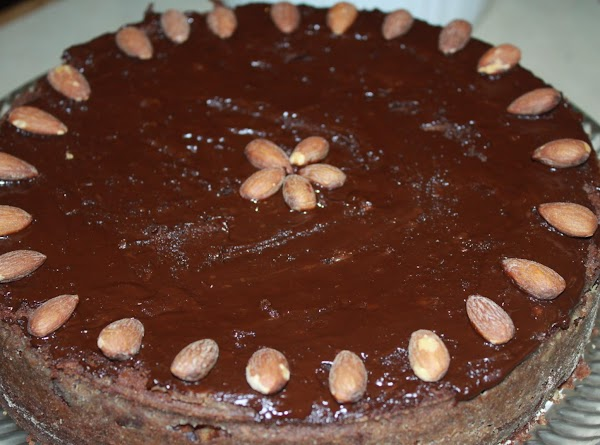 Melt the icing ingredients and spread on top of cool cake.Decorate with additional almonds.