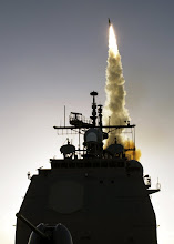 Photo: 031211-N-0000X-001 Kauai, Hawaii (Dec. 11, 2003) -- A Standard Missile-3 (SM-3) is launched from the Aegis cruiser USS Lake Erie (CG 70) as part of the Missile Defense Agency's latest Ballistic Missile Defense System (BMDS) test to defeat a medium range ballistic missile threat. The SM-3, part of the Aegis Weapon System intercepted a target launched from the Pacific Missile Range Facility, Barking Sands, Kauai, Hawaii at an approximate speed of 3.7 kilometers per second. The two missiles collided several hundred kilometers from Kauai at an altitude of approximately 137 kilometers. The BMDS test included evaluation of the long-range surveillance and tracking capabilities of two Navy ships, the effective communications between the ships and command and control units in Colorado, and the launch of the SM-3 interceptor. This was the fourth successful intercept for the sea-based element of the BMDS. U.S. Navy photo. (RELEASED)