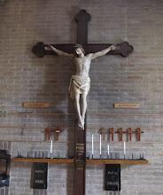 Photo: Het kruisbeeld met corpus acherin onze kerk is afkomstig uit de vorige kerk. In 1925en in 1939 werd het kruis van de muur afgehaald en voorin de kerk geplaatst, dit staat ook op het kruis geschreven.  Er werd in 1925 en in 1939drie dagen gebeden in de kerk waarna het op de derde dag opnieuw achterin de kerk werdterug geplaatst.Duizenden mensen bezochtenin deze periode van drie dagen de kerk om te bidden, om te luisteren naarprekenen om geld aan de missie te doneren.  Rondom het kruisbeeldhangen kleinekruisjes met daarop de namen van overledene die vanuit onze kerk zijn begraven.Wij herdenken hieronze overleden parochianen.Na afloop van de Echaristievieringopallerzielen mogen nabestaanden deze kruisjes mee naar huis nemen.  The cross in the back of our church was originally made for and used in the previous church that was built on the same location.  In 1925 and 1939 the cross was removed from the wall and placed in the front of the church. In those years people prayed for three consecutive days and on the third day the cross was returned to its place in the back of the church. During these three days thousands of people visited the church to pray, donate money to the Mission and to listen to the priest who was preaching.  The cross is surrounded by small crosses. Each small cross contains the name of someone from our parish who died this year. This way we remember this person. After mass on All Souls the family of the deceased is allowed to take the small cross home.